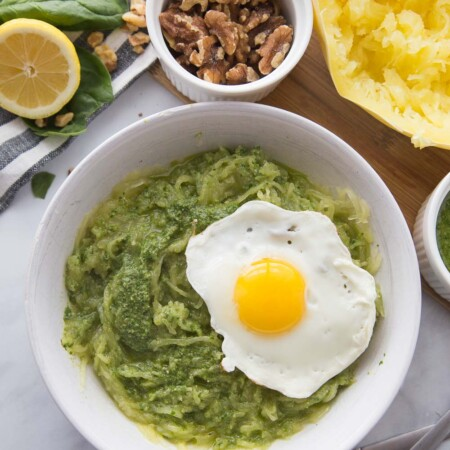A white bowl with spaghetti squash pesto and a fried egg
