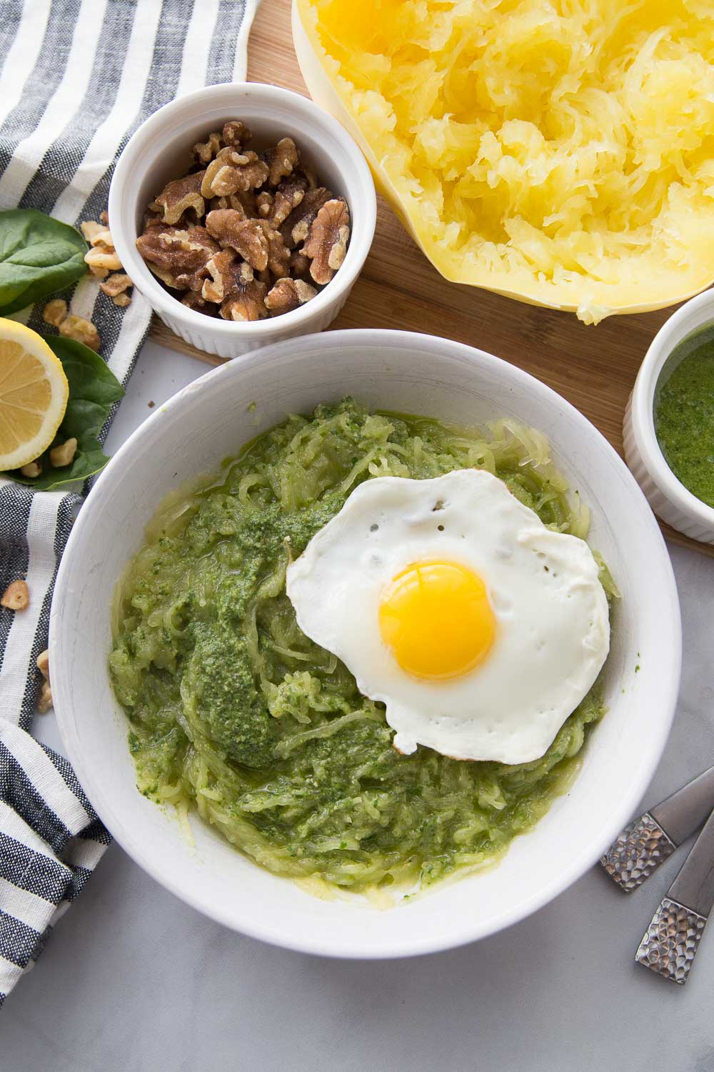 A white bowl of spaghetti squash with pesto and a fried egg