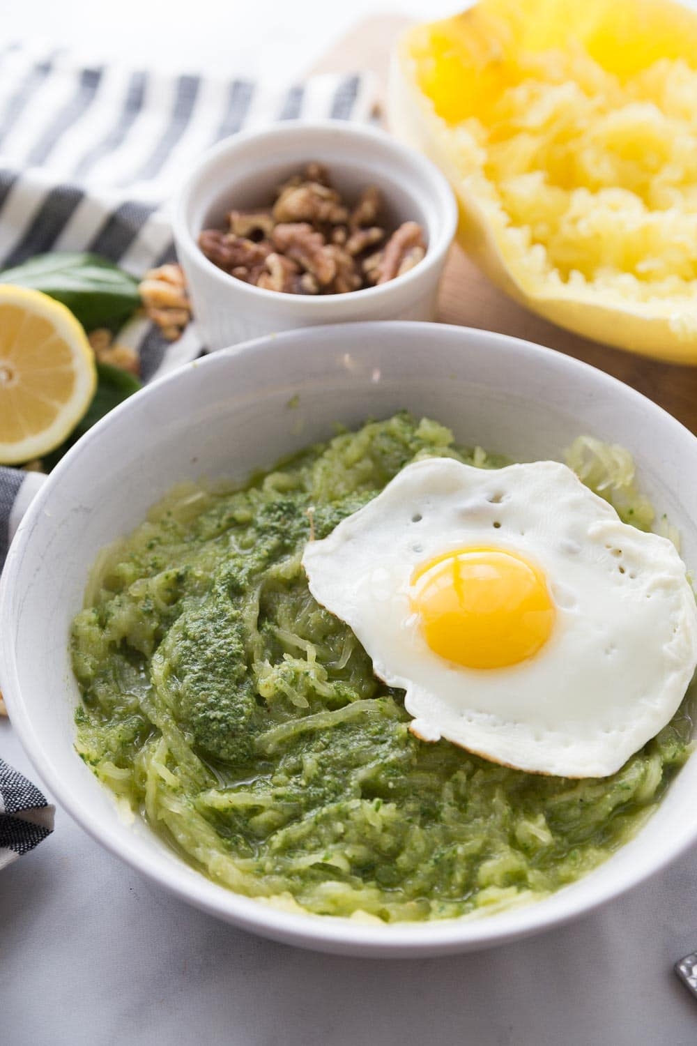 A white bowl with spaghetti squash pesto and a fried egg on top