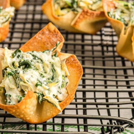 Filled spinach artichoke cups on a cooling rack