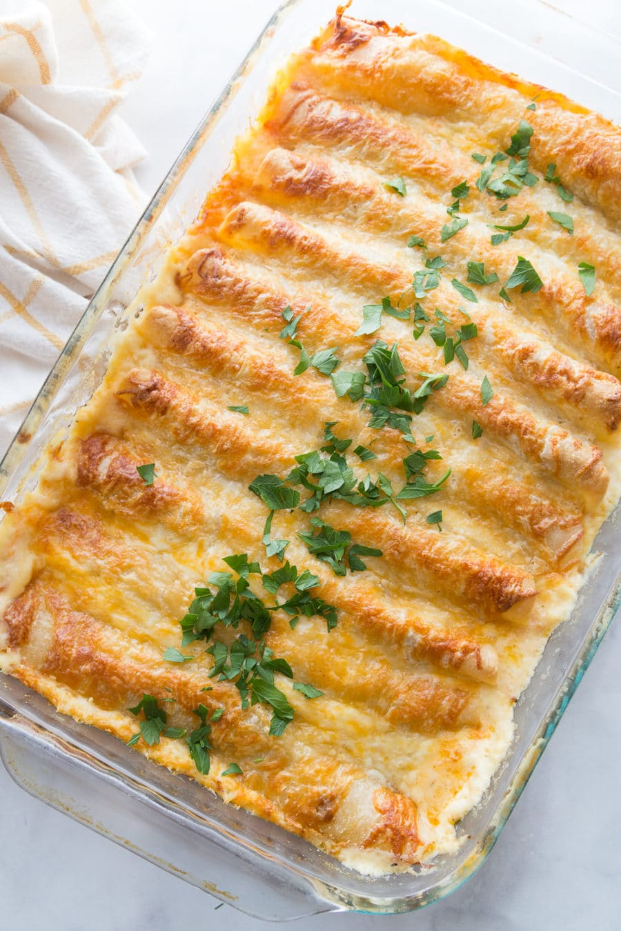 A pan full of white chicken enchiladas topped with cheese