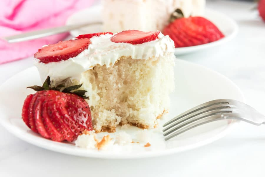 A close up piece of strawberry poke cake