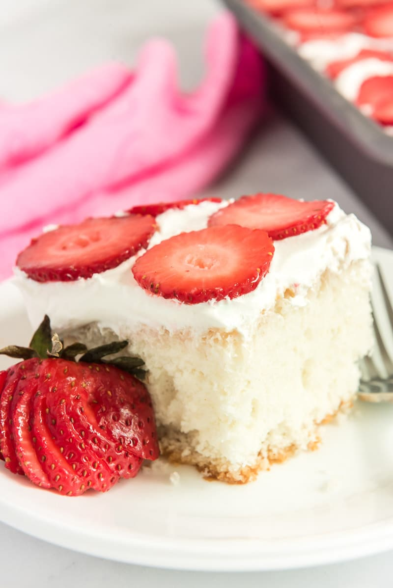 A square piece of strawberry poke cake