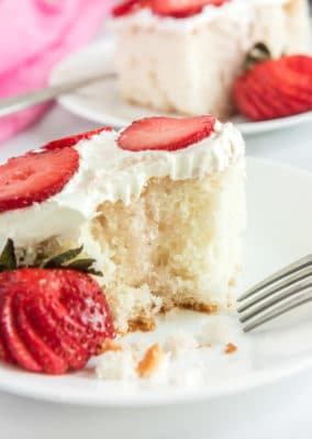 Strawberry poke cake with whipped cream on top