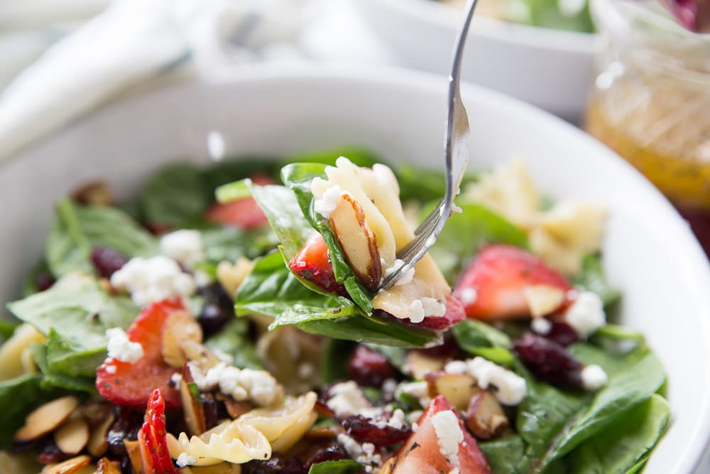A fork full of strawberry spinach salad
