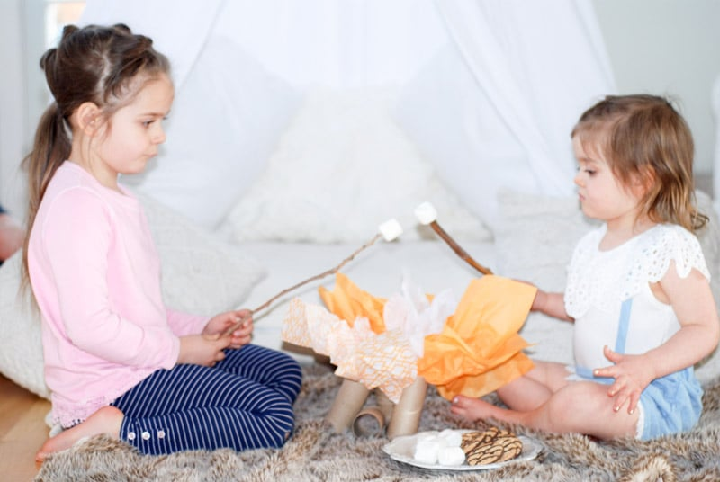 Kids camping indoors and roasting marshmallows