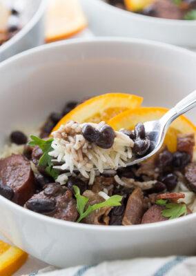 Spoon full of feijoada above a bowl full of feijoada