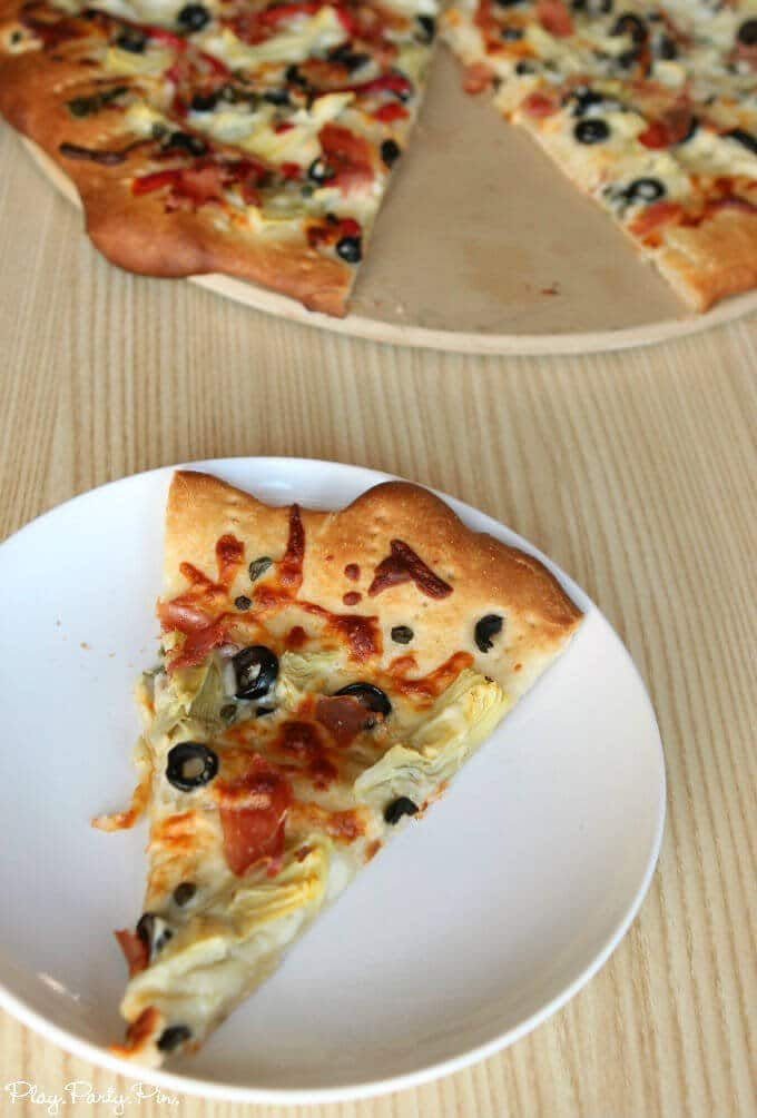 Perfect pizza recipe from playpartyplan.com with plenty of veggies, meats, and double cheese