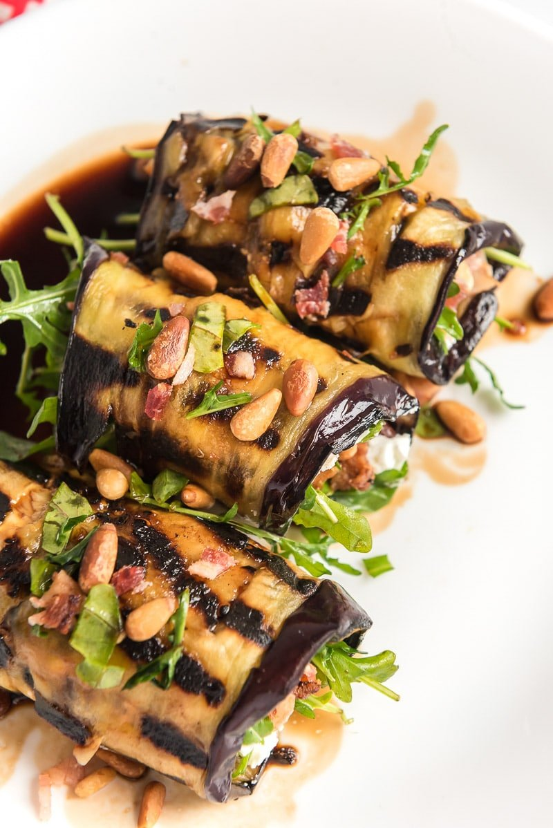 Eggplant rolls with pine nuts and bacon on top