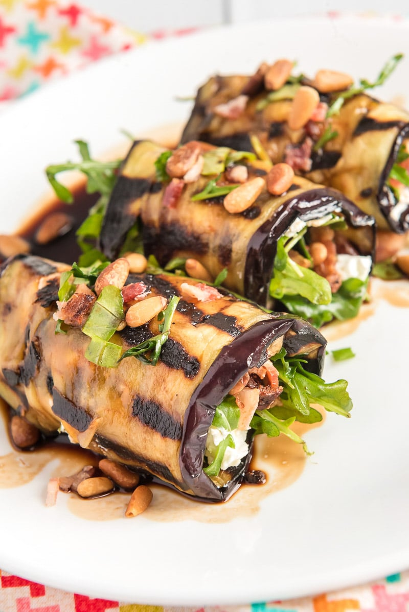 Three eggplant rolls filled with arugula and bacon