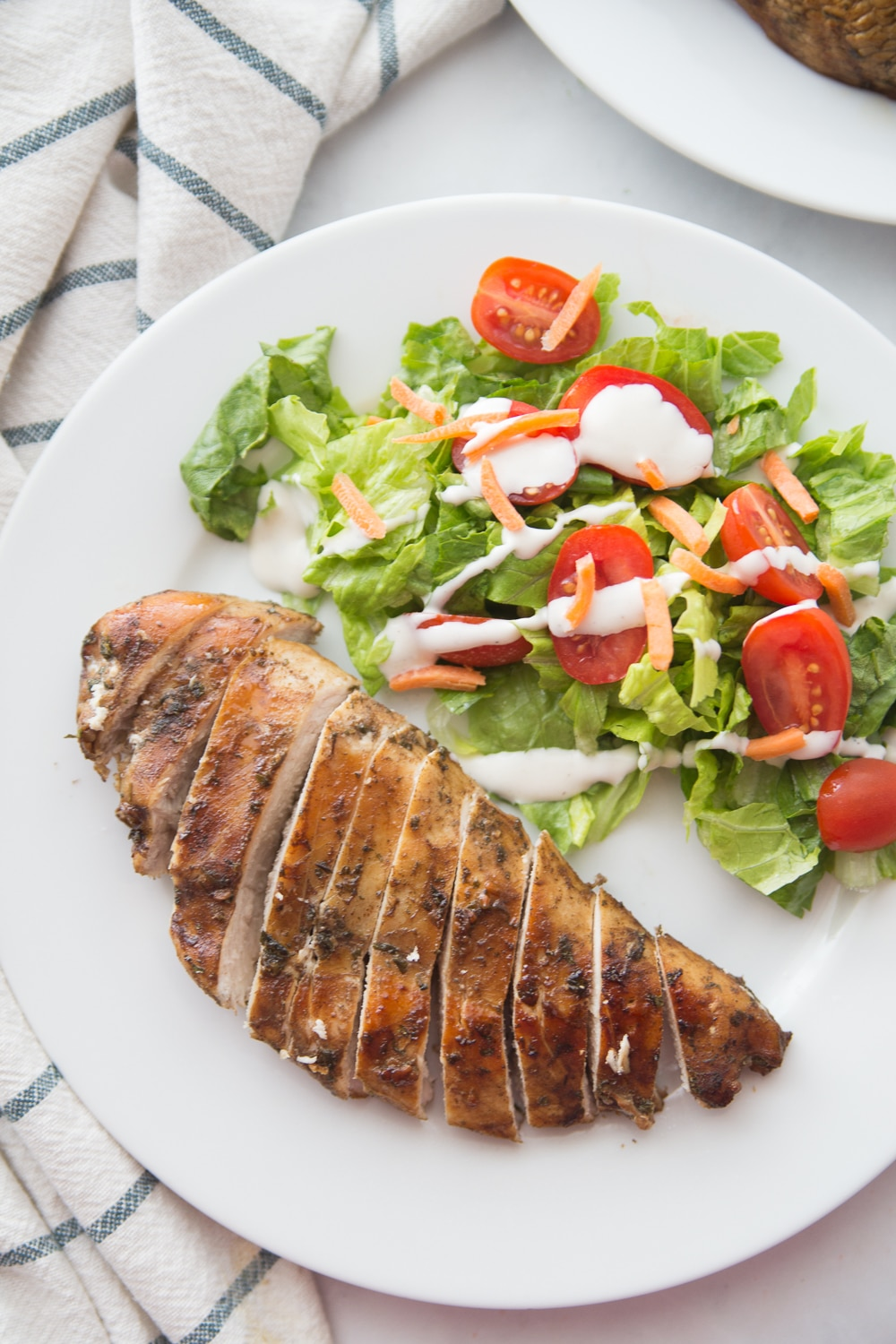 Sliced balsamic grilled chicken on a plate with salad