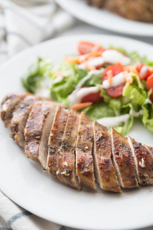 Sliced baked balsamic chicken on a white plate
