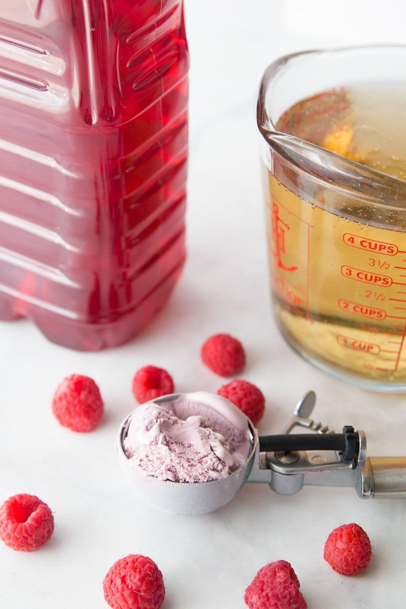 A scoop of raspberry sherbet and other ingredients for sherbet punch