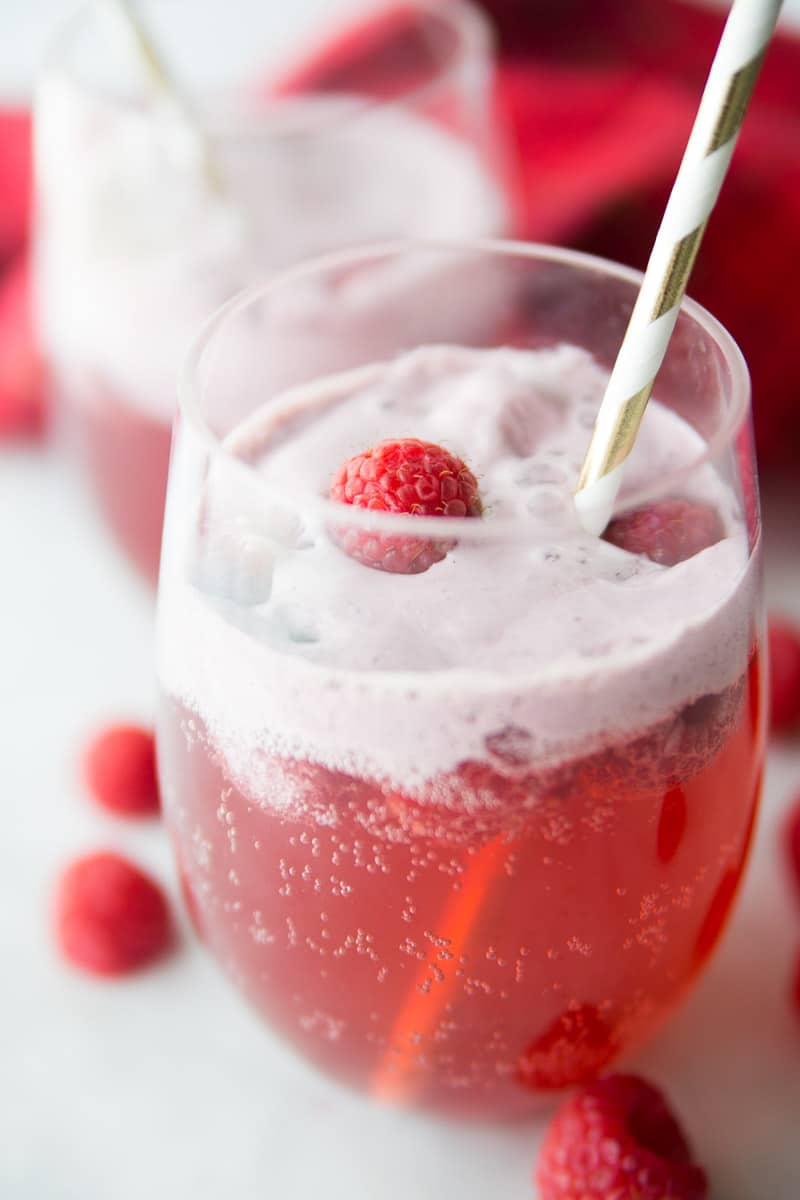 A glass of non alcoholic holiday punch with a straw