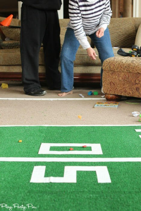 Fun Super Bowl party games like this one where you have guests try to toss things to get them to land on football field lines!