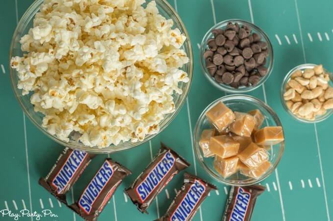 This Snickers popcorn looks amazing. Popcorn mixed with chocolate, caramel, peanuts, and of course chunks of Snickers!