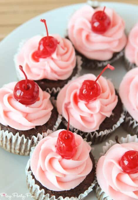 Cherry coke cupcakes topped with a cherry buttercream frosting
