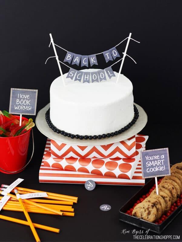 White cake, pencils, and a cake stand with chalkboard printables
