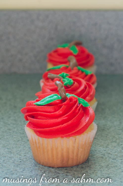 yellow cupcakes with red frosting and green chocolate leaves