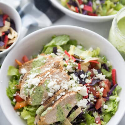 Two bowls of southwestern chicken salad with dressing