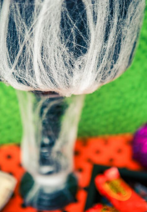 Easy DIY Halloween treat stand made with foam, paper straws, and spiderwebs! Cute Halloween party decorations!