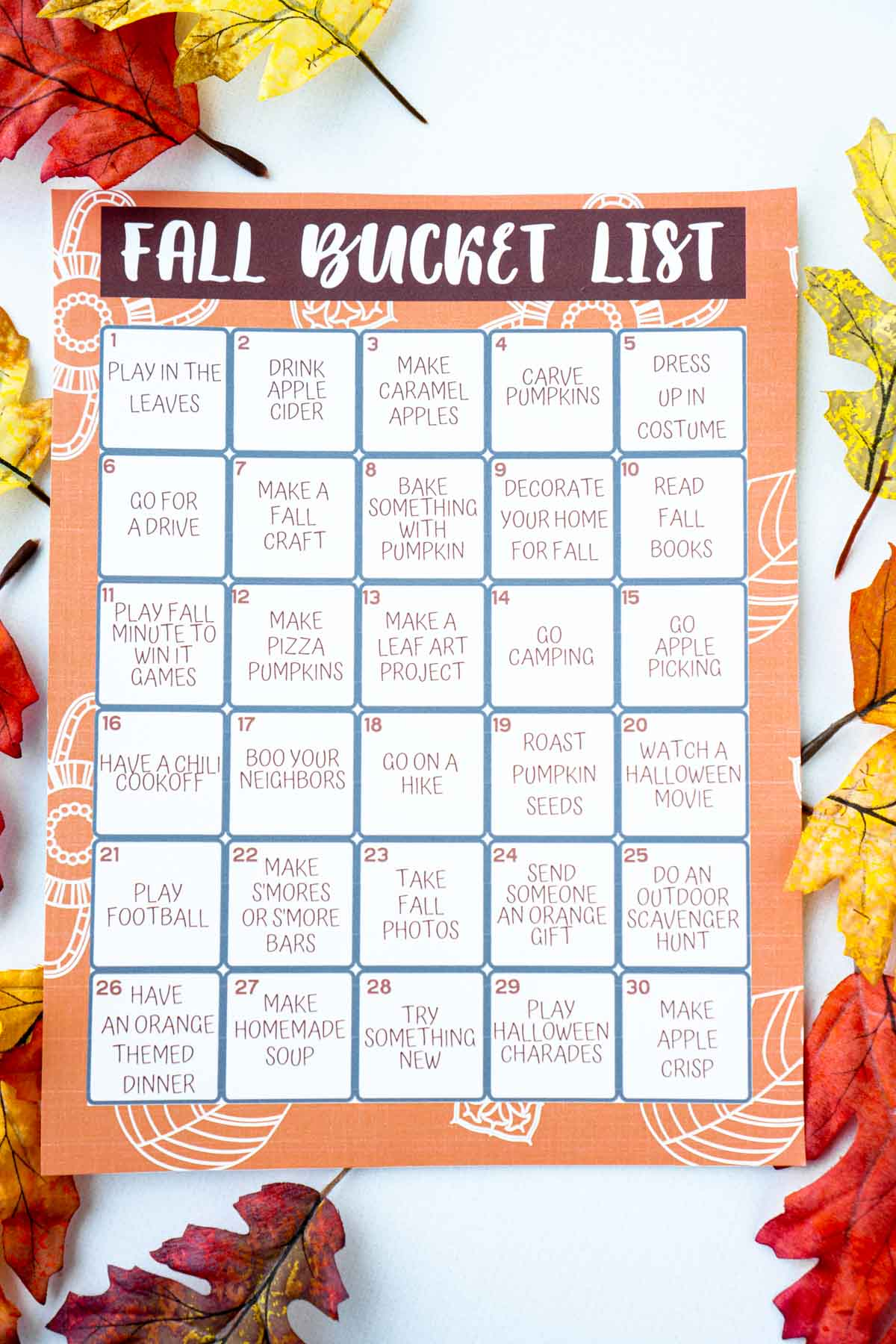 A fall bucket list calendar on top of a bunch of fall colored fake leaves