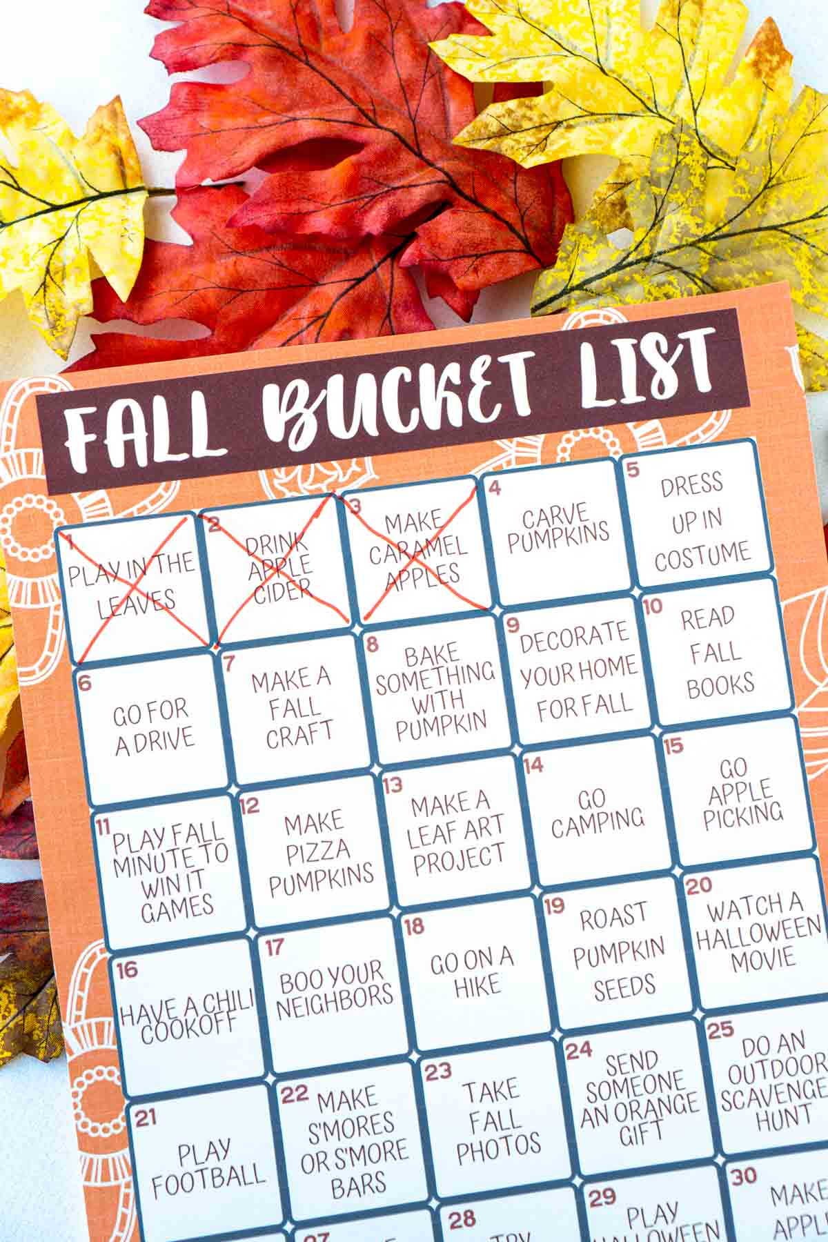 A fall bucket list with three items marked off on top of fake leaves
