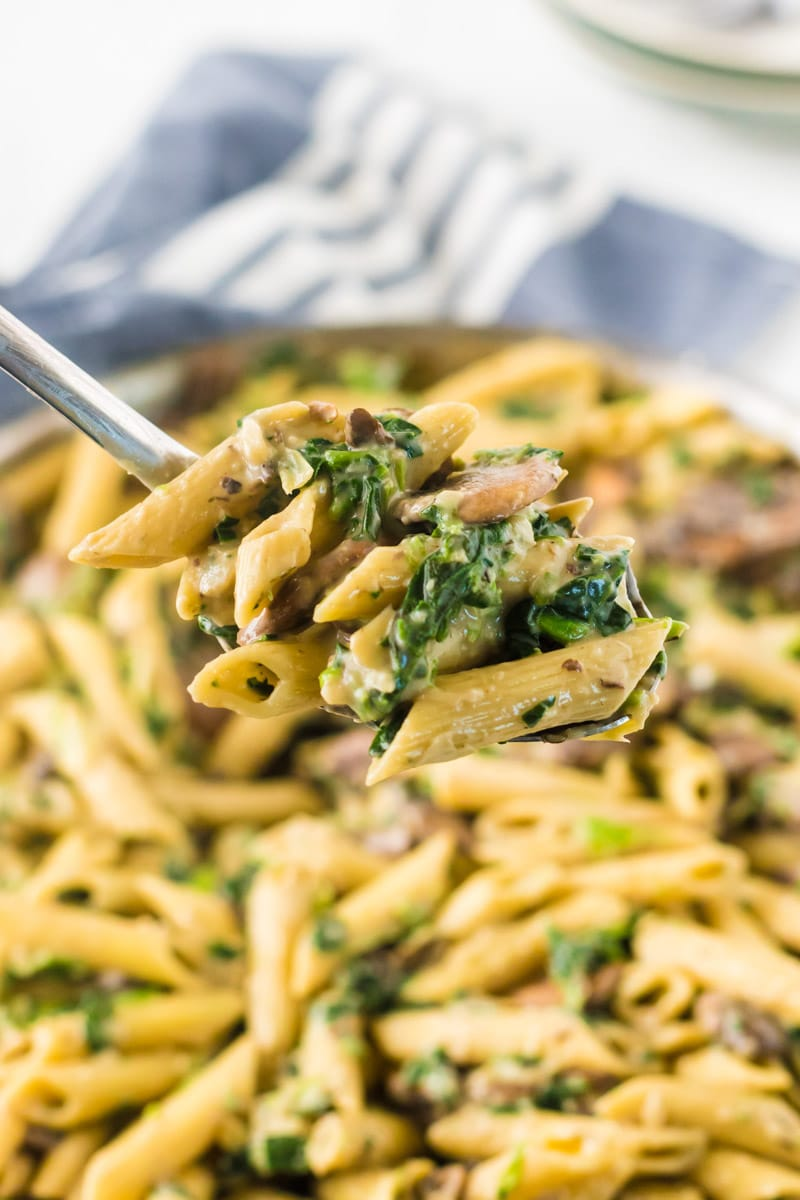 Fork full of spinach and artichoke pasta