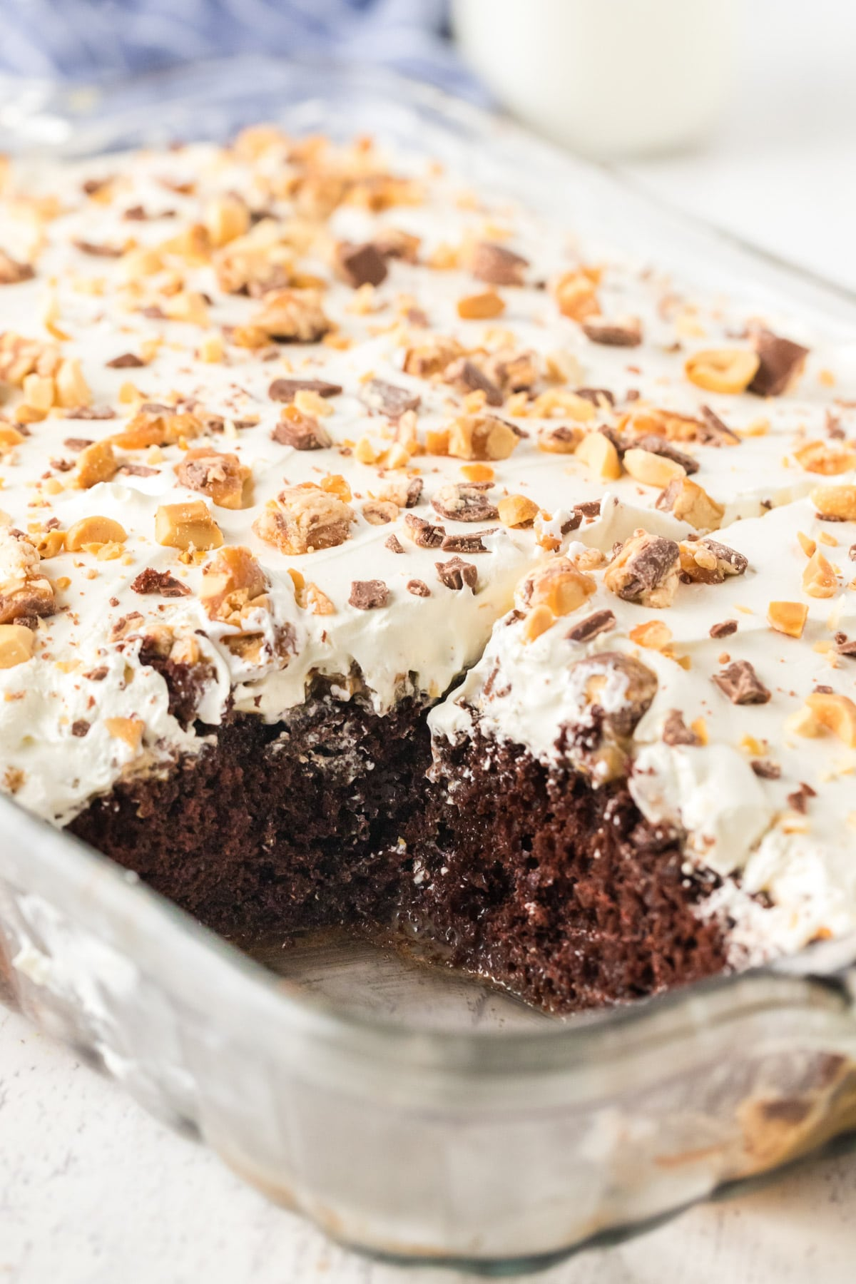 Snickers poke cake with a piece cut out