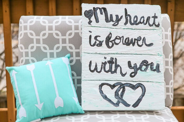 This faux pallet sign is one of the easiest DIY crafts ever! Just pick out a song from your wedding, one of your favorite love quotes or lyrics from your favorite music then get started. It would be the perfect way to tell someone I love you or even as a decorating idea for a rustic wedding! I still can't believe what it's actually made from; I never would've guessed!