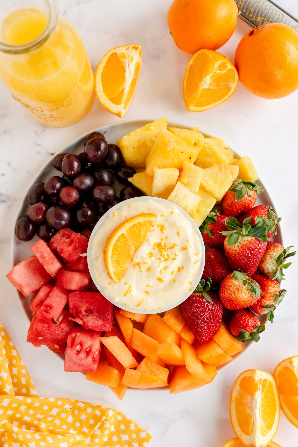tray of fruit with a bowl of fruit dip in the middle