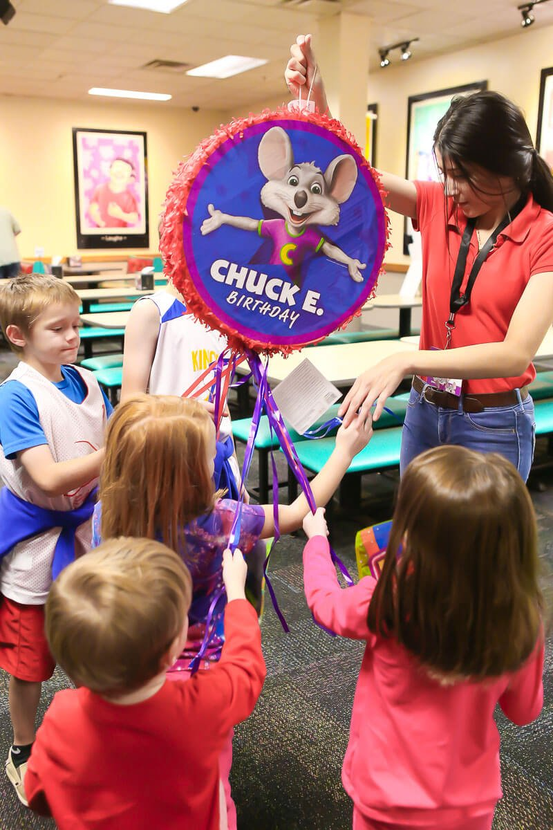 Pulling the strings on a Chuck E Cheese birthday pinata