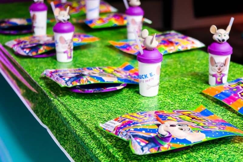 A table set with collectible cups for a Chuck E Cheese party