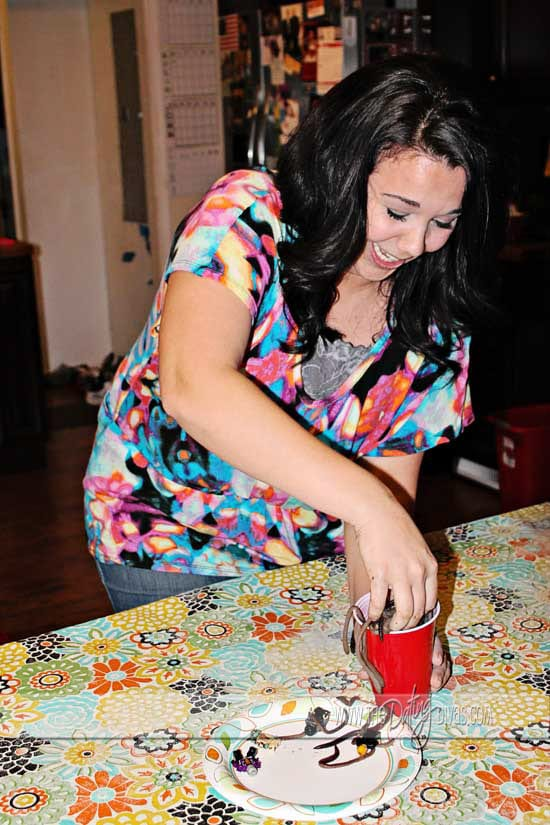 Reaching into a cup of worms in fun Halloween games for adults