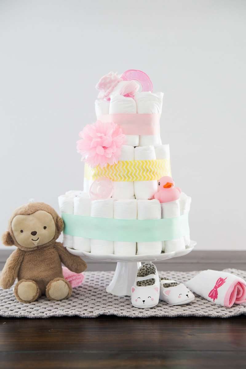 A simple DIY diaper cake tutorial showing you in photos and video how to make a diaper cake as well as other great diaper cake ideas! Learn how to make an easy diaper cake in just a few minutes.