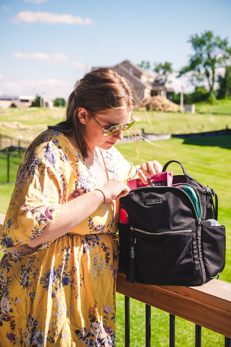 Mom getting something out of Lily Jade diaper bag