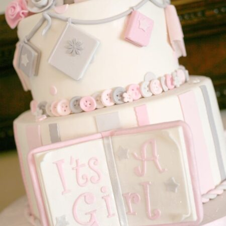 A white it's a girl cake with a cake book in front