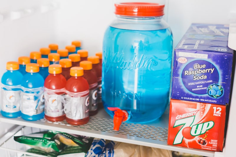 Red white and blue drinks loaded onto metal shelves in the Gladiator All Refrigerator