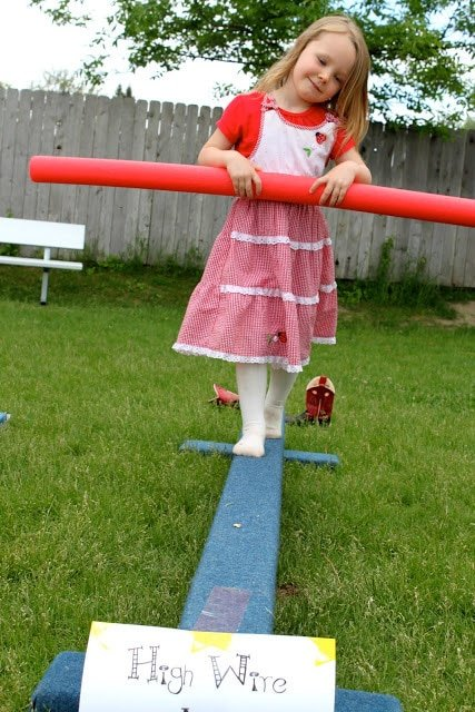 A girl walking a hire wire at a circus party