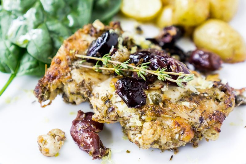 A piece of baked lemon chicken with olives and rosemary on top