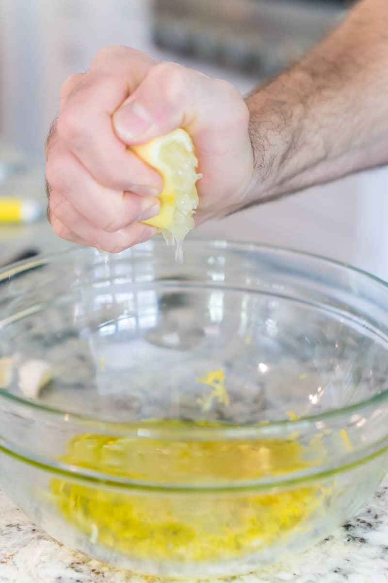 Squeezing a lemon into a Greek chicken marinade
