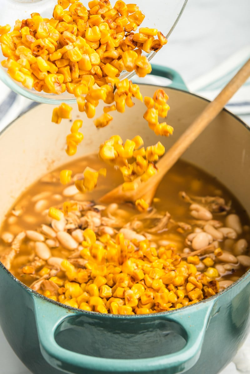 Adding corn to make the best white chicken chili