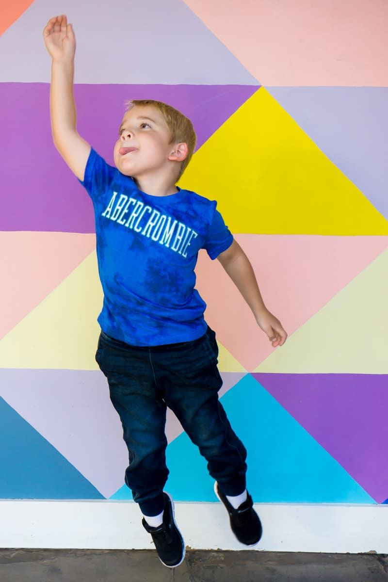 Kid jumping in front of a wall while getting ready for kindergarten