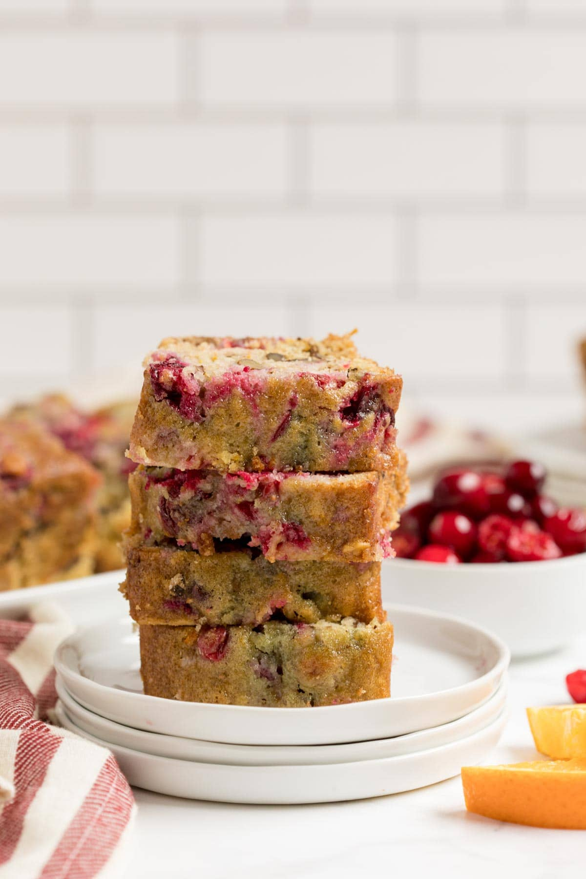 Sliced pieces of cranberry orange bread on a stack of white plates