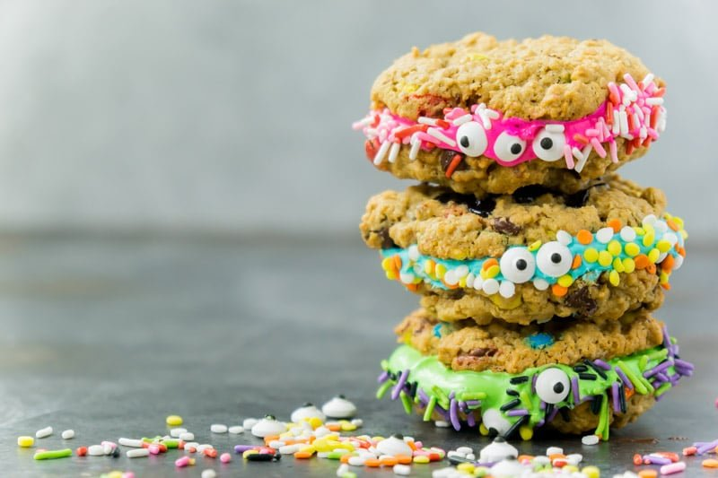 Monster cookie sandwiches stacked in a Halloween party food display