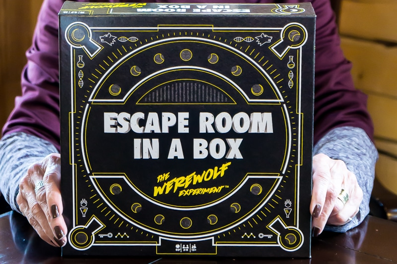 A woman holding Escape Room in a Box game