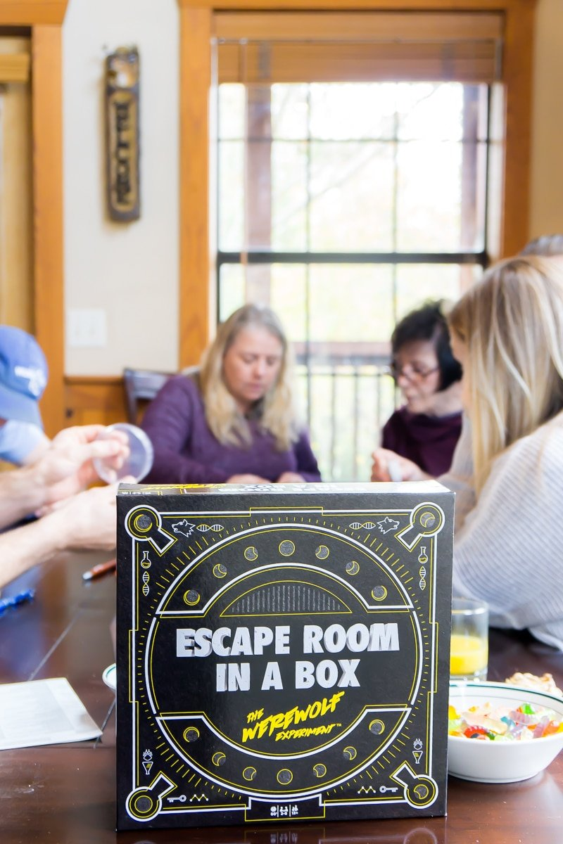Adults playing the best escape room board game - Escape Room in a Box