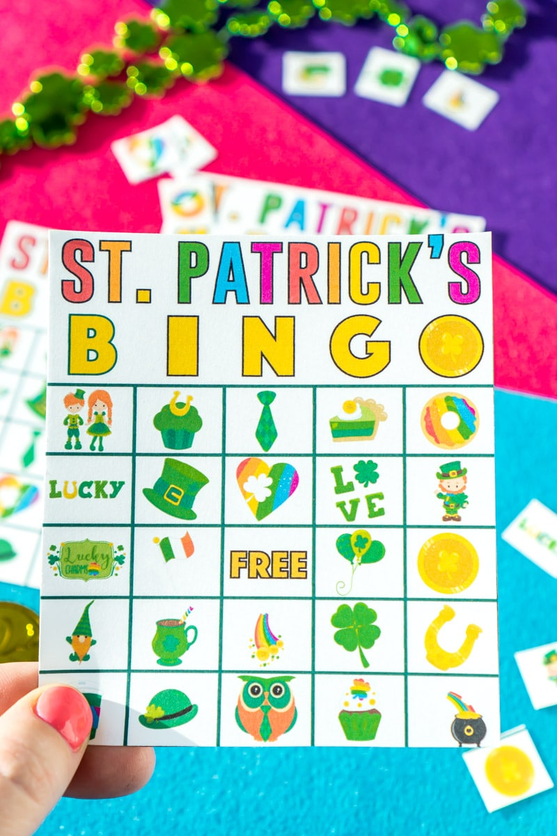 A hand holding one of many St. Patrick's Day bingo cards
