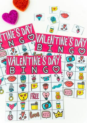 Three Valentine bingo cards with markers and master callers