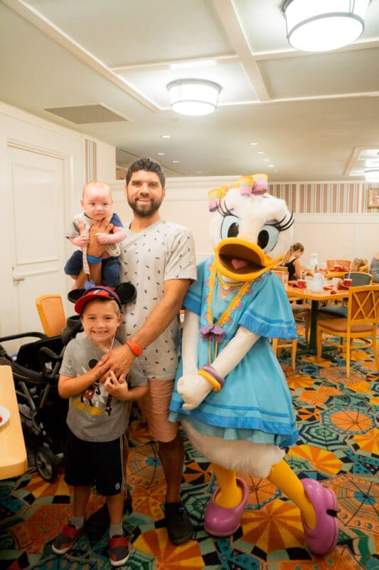 Family standing with Daisy Duck in blue dress